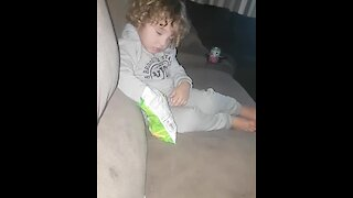 Kid struggles to stay awake to eat chips