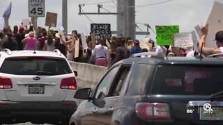 Protesters march across Roosevelt Bridge in Stuart