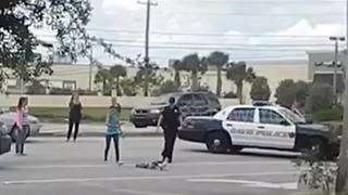 Police officer stops traffic for duck family crossing road - Video