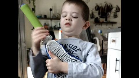 4 year old has epic air guitar session with toy lacrosse stick