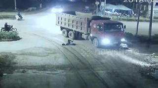 Scooter driver cheats death after rolling under lorry - Video