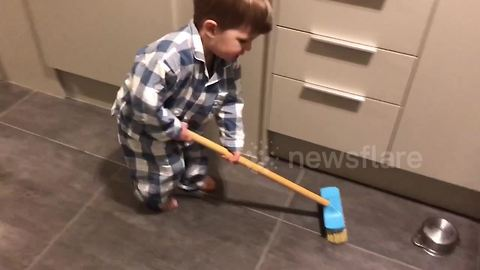 Toddler prepares for Winter Olympics curling in kitchen