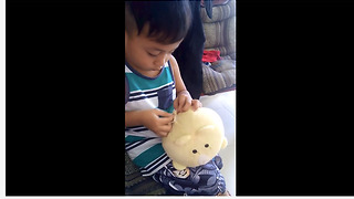 Skillful little boy sews together his damaged stuffed animal