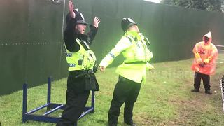 Police officers dance in front of festival-goers at Camp Bestival - Video