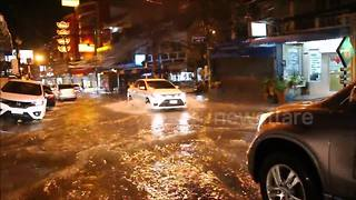 Vehicles battle through flooded roads after downpours in Thailand coastal city