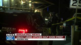 Heavily armed officers shut down street - Video