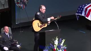 Fr. Tim Plavac performs an original song at the public funeral service for Officer Mathew Mazany