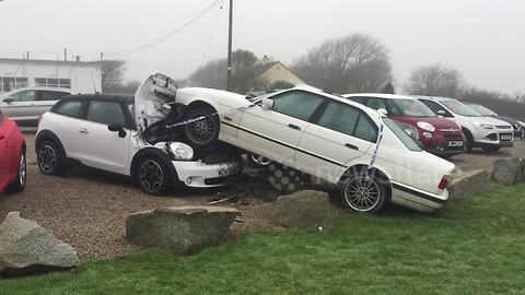 BMW leaves road and crashes into Mini on garage forecourt