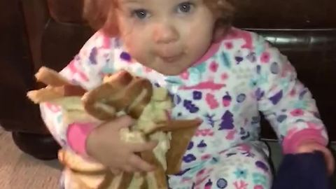 Little Girl Crawls Around Eating and Holding Onto Bread