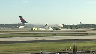 Atlanta Airport Firefighters Spray Foam on Delta Plane's Smoking Engine - Video