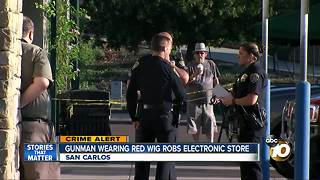 Gunman wearing red wig robs electronic store - Video