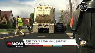 Trash truck rolls down street, pins driver - Video