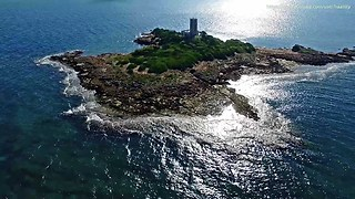 Lonely lighthouse island in Greece seen from drone