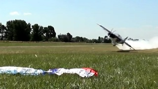 Low-flying plane picks up flags off the ground - Video