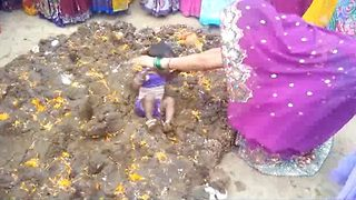 Parents dip children in cow dung in bizarre good luck ritual in India - Video