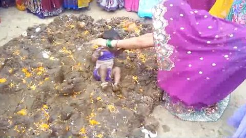 Parents dip children in cow dung in bizarre good luck ritual in India