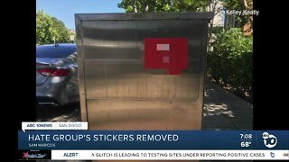 Neighbors quickly rip down white supremacist stickers