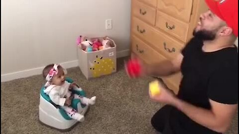 Baby laughs along to her dad's juggling act