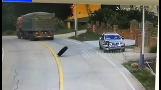 Tyre falls from lorry and lands on roof of parked car with driver inside - Video