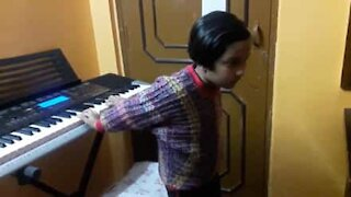 Seven-year old plays piano lying down and backwards