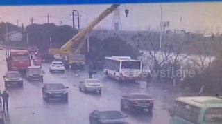 Crane driver rescues passengers trapped in sinking bus - Video