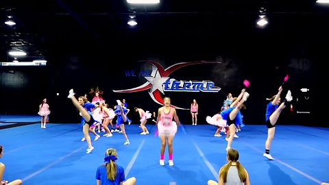 Cheer team use performance for coach's baby gender reveal