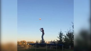 Young Boy Jumps On A Trampoline With A Ball - Video
