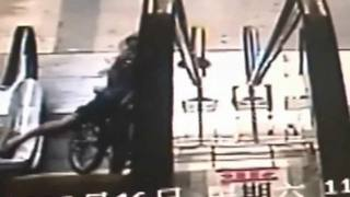 Boy on bike falls down escalator - Video