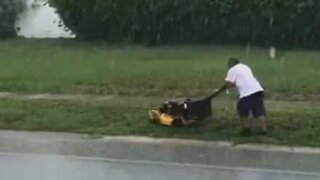 Rain won't stop this man from mowing his lawn