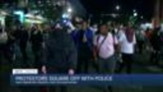 Protestors square off with police after peaceful vigil for slain father