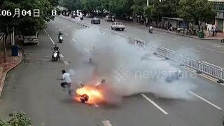 Two men leap off moving scooter after it bursts into flames on busy road