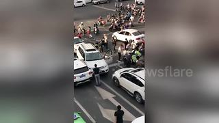 Erratic SUV driver crashes into scooter riders waiting at traffic lights - Video