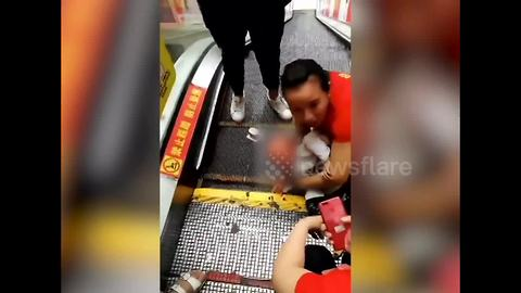 Where are the parents? Toddler LYING DOWN on escalator gets hand stuck