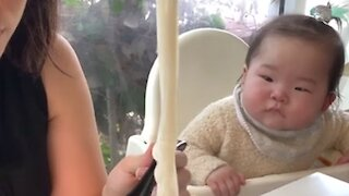 Adorable baby can't stop drooling when watching mom eat noodles