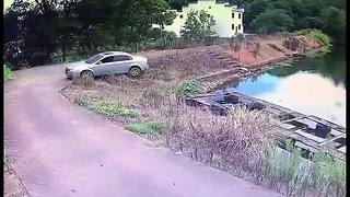 Driver forced to swim back to shore after reversing into reservoir - Video