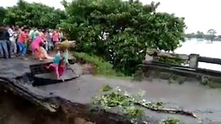 Horrific moment mother and daughter swept away in overflowing river after bridge crumbles  - Video