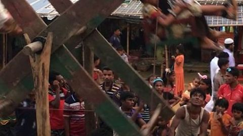 Children Play on Ferris Wheel in Refugee Camp After Pause in Monsoon