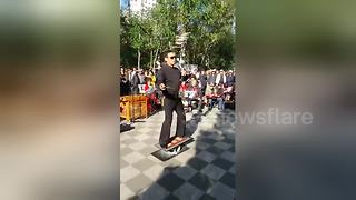 Man stands on balance plate while playing Chinese instrument - Video