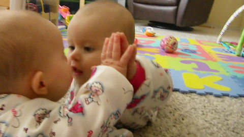 Baby attempts to kiss her own reflection