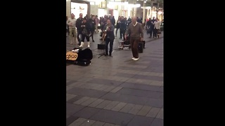 Elderly gentleman dances to street performer