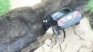 Car falls into crevasse after heavy rains in Renville County - Video