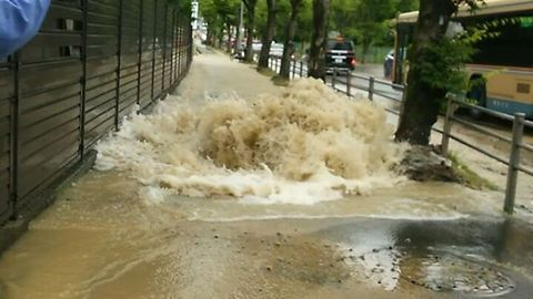 Water Surges Onto Pavement From Burst Pipe Following Japan Earthquake