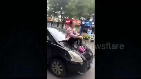 Disgruntled woman sits on hood of husband's moving car
