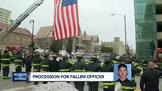 Fallen officer carried to Medical Examiner in police procession