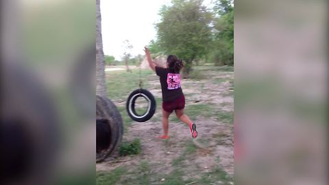 A Teen Girl Runs And Jumps Onto A Tire Swing And Ends Up On The Ground