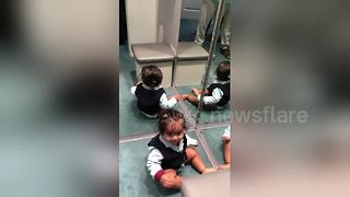 Baby boy left adorably confused by his reflection - Video