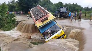 Bus washed off road after flash flood in Thailand - Video