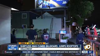 Shirtless man climbs billboard, jumps rooftops - Video