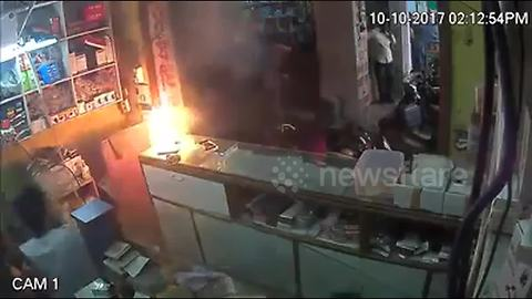 Shop employees run for cover as mobile phone explodes