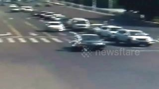Motorcyclist double somersaults through air after running red light - Video
